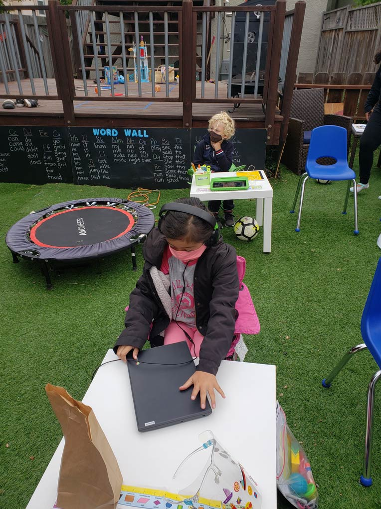Two students wearing masks in the outdoor learning pod space