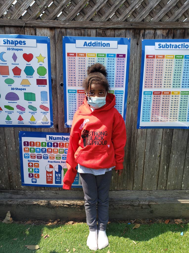 "A young Black female student standing in front of addition and subtraction table posters, wearing a red ""STRONG, BLACK, PROUD"" hoodie"