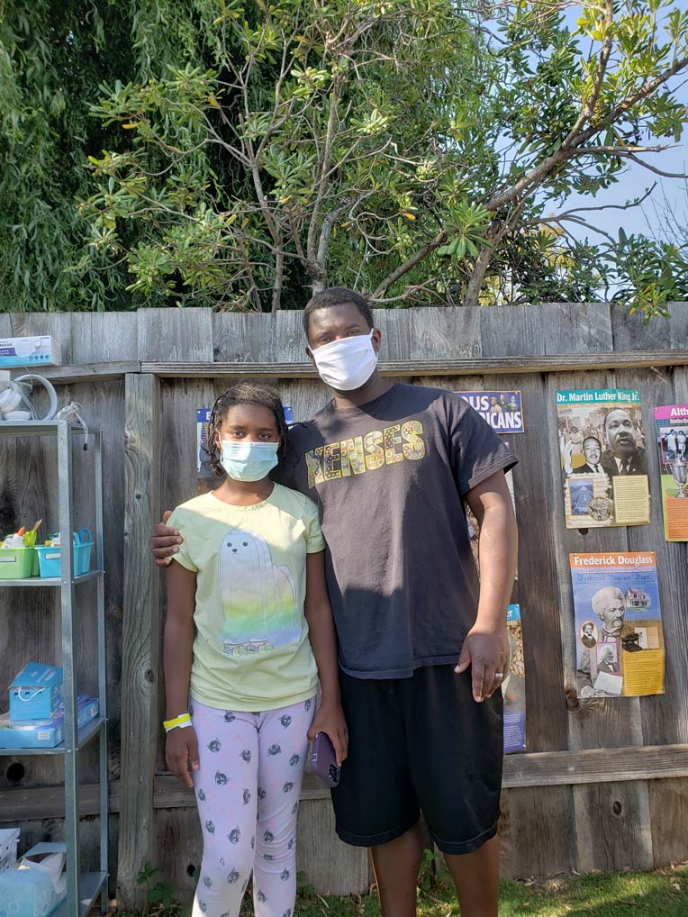 Brian Doss and one of his daughters standing together wearing masks